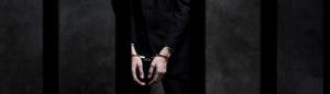 Man handcuffed behind bars